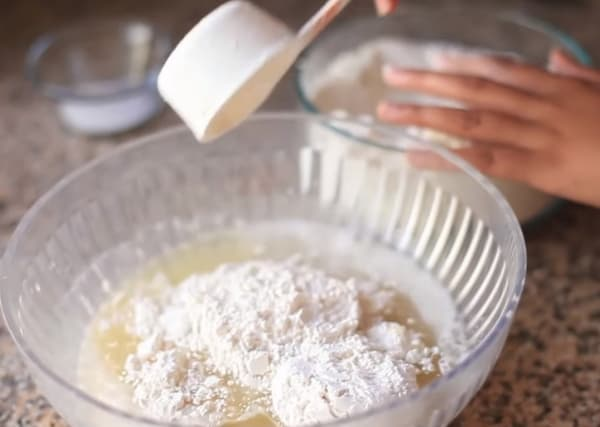 putting flour to yeast mixture for pandesal recipe