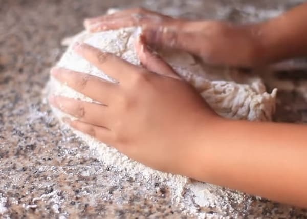 kneading pandesal dough with two hands