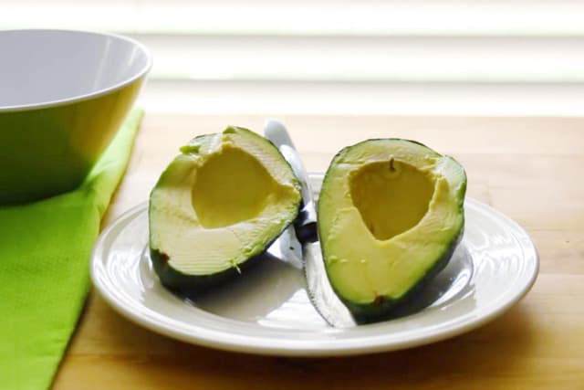 one ripe avocado cut in halves placed on a white plate