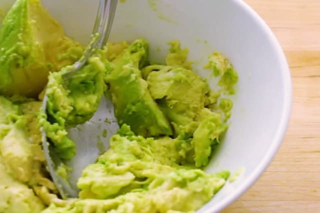 mashed avocado on a medium white deep bowl using a spoon
