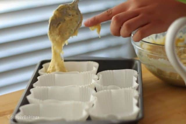 putting the batter of the french breakfast bread in individual mini bread liners