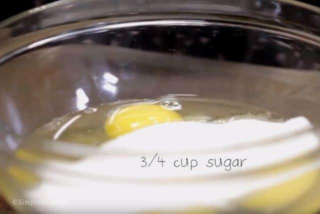 adding sugar into the eggs in a glass bowl