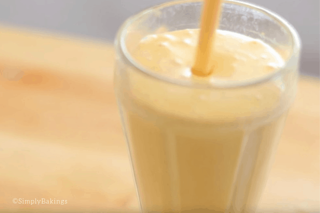 pouring the delicious and refreshing mango shake in a tall glass