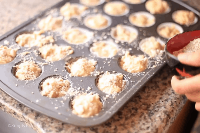 putting oatmeal streusel topping on top of mini banana muffin batter