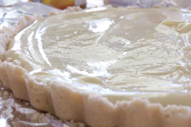 adding the pie cream mixture onto the pie crust of the White Chocolate Fruit Tart