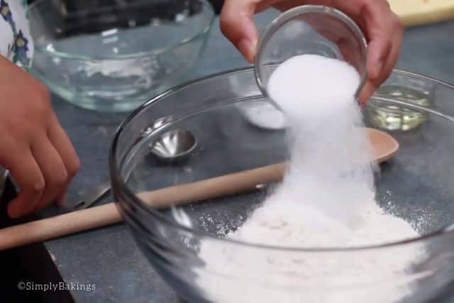 adding sugar to the flour