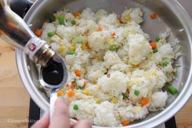 seasoning the fried rice with soy sauce