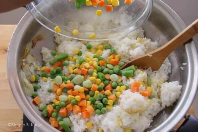 adding the frozen vegetables to be cooked with the rice and egg