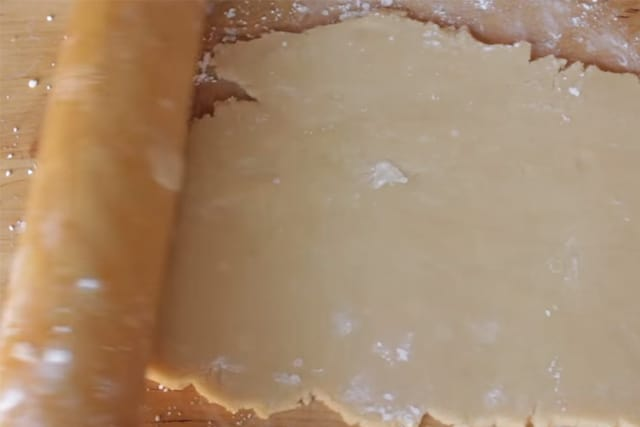 flattened cookie dough with a rolling pin