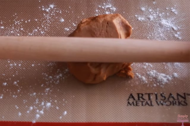 rolling out the cookie dough using a wooden rolling pin