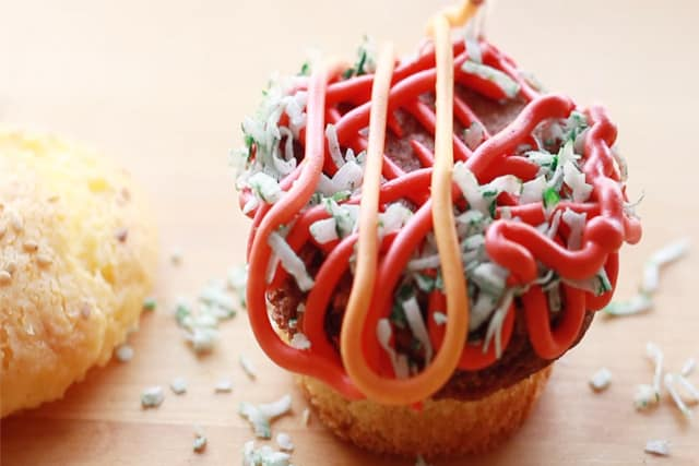 adding red and orange frosting to the hamburger cupcake