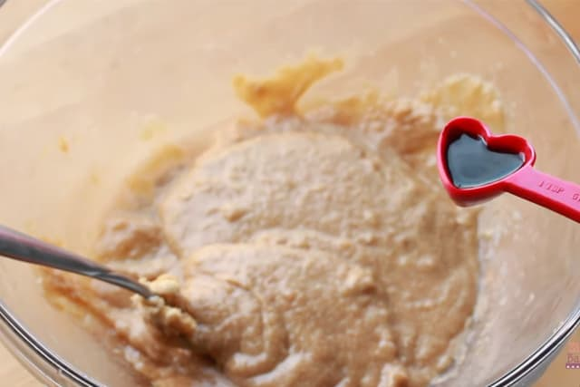 adding red food color to the cookie batter