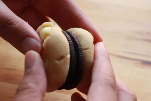 inserting the Oreo between 2 cookie dough balls