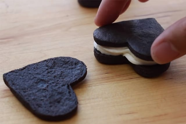 putting another oreo cookie on top of the cream filling
