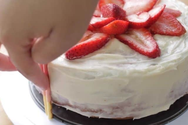 decorating the cake with strawberry pocky sticks
