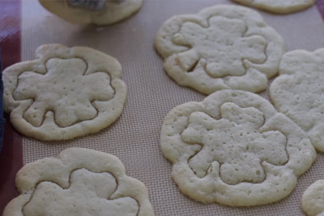 cutting out the cookies using a shamrock cookie cutter