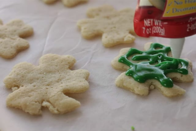 frosting the cookies with green cookie icing