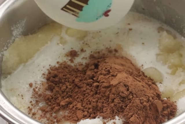 mixing cocoa powder and milk to ingredients of no bake oatmeal cookie recipe