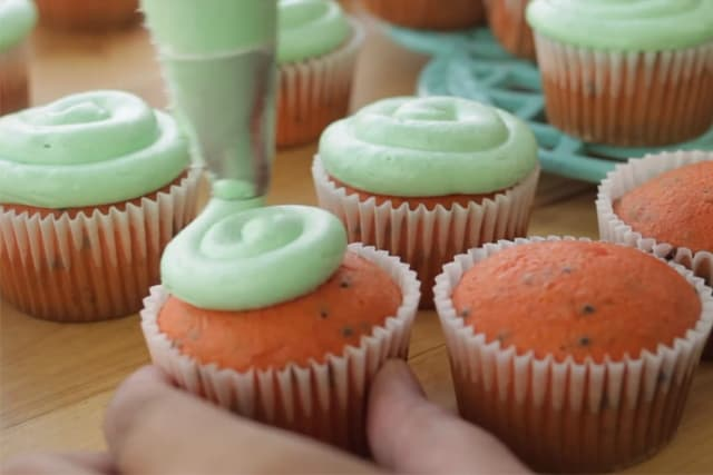 frosting the watermelon cupcakes with buttercream frosting