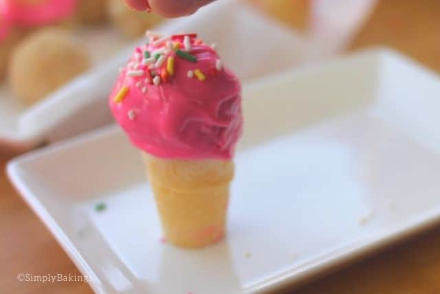 coating the cake pops with colorful chocolate candy melts and sprinkling with candy sprinkles