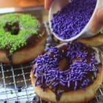 pouring candy sprinkles onto Halloween donuts
