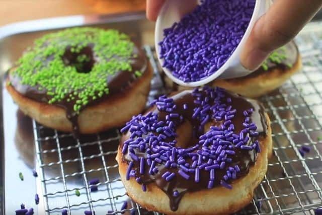 sprinkling colorful candy sprinkles on the Halloween donuts