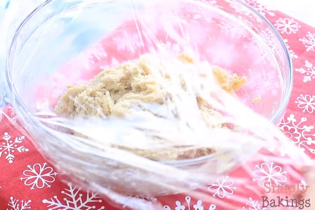 covering the eggnog cookie dough with saran wrap