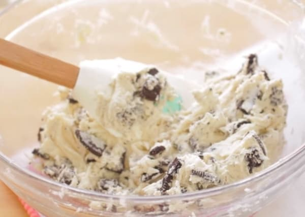 folding in crushed oreos to the ingredients of oreo cheesecake cookies