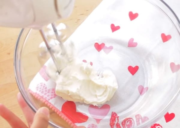 whipping cream cheese in a mixing bowl