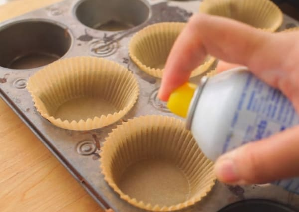 spraying the cupcake liners for 3 ingredient cupcake recipe