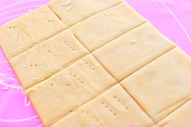 brushing egg wash to the pastry crust and poking holes on them