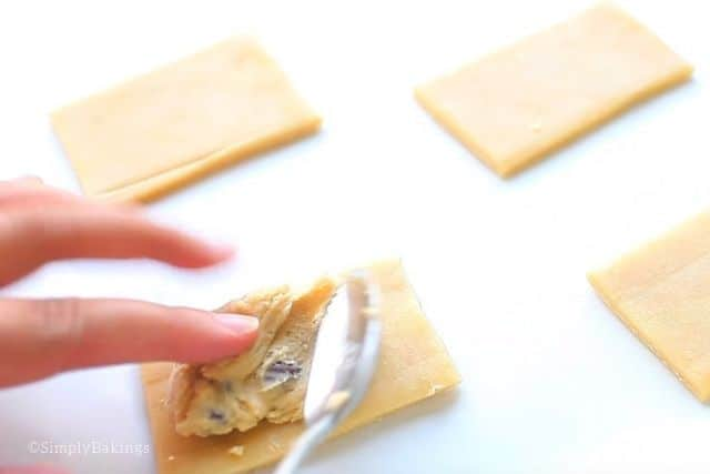 putting chocolate chip filling to individual pastry crusts