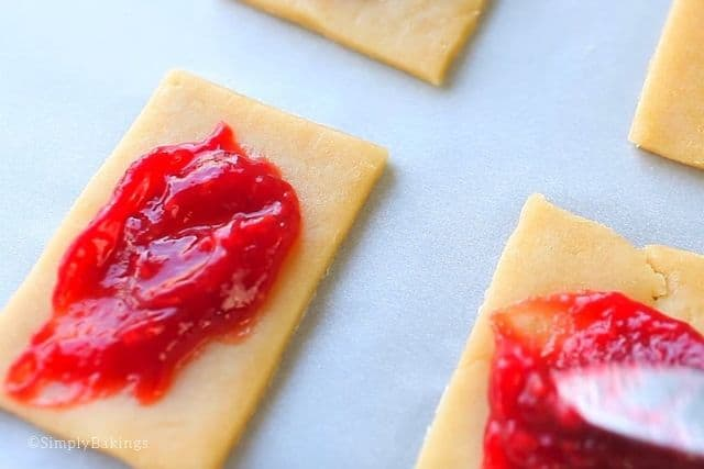 putting cranberry jam on each pastry crust