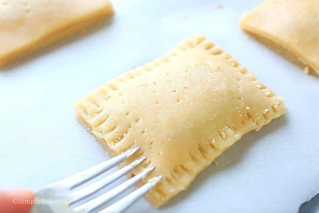 covering the pastry crust and sealing it using a fork