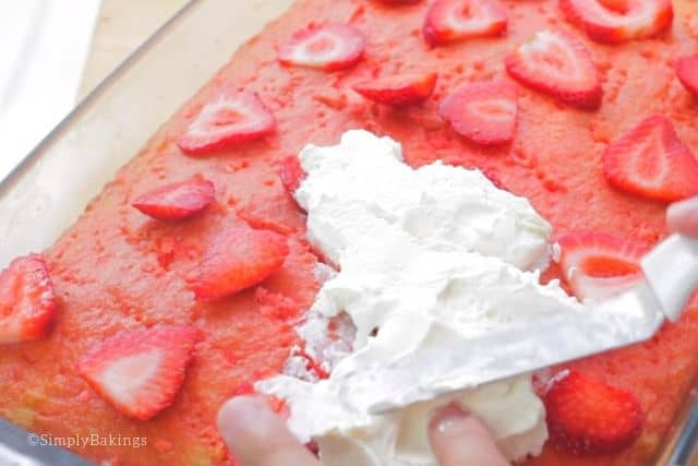 topping the cake with fresh strawberries and whipped topping