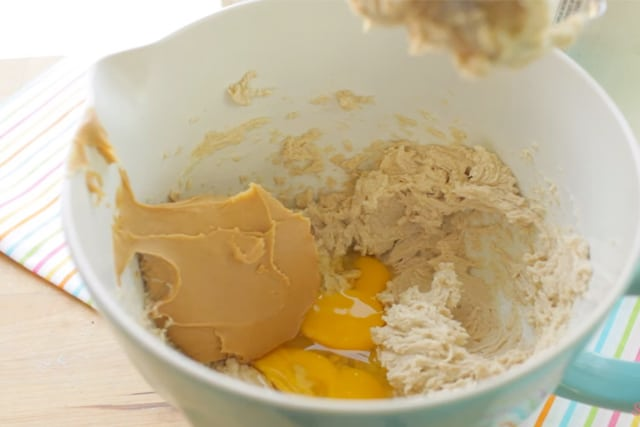 adding eggs, vanilla and peanut butter to the butter and sugar mixture