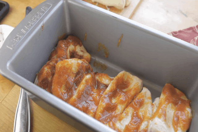 layering the pumpkin pull part bread in a loaf pan
