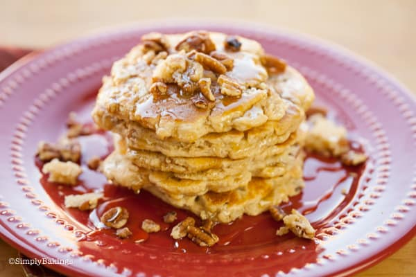 pecan pancakes on a red plate topped with chopped pecans