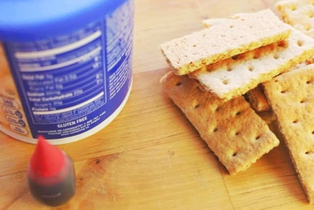 red food color, white frosting, and graham crackers for edible band aid recipe