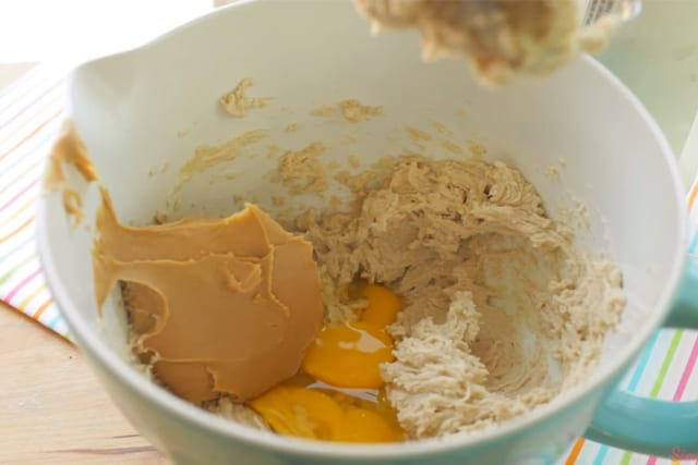 adding in the creamy peanut butter and eggs to the butter and sugar mixture