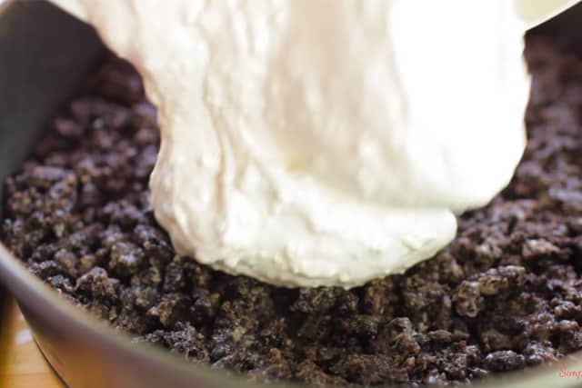 pouring the cream cheese mixture on top of the Ore crust for the No Bake Oreo Cheesecake