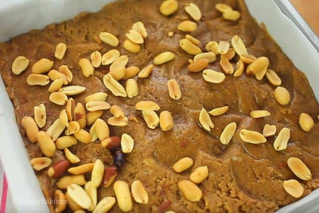 garnishing the vegan peanut butter blondies with whole peanuts