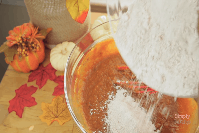 combining the wet and dry ingredients for pumpkin chocolate chip bread in a clear mixing bowl