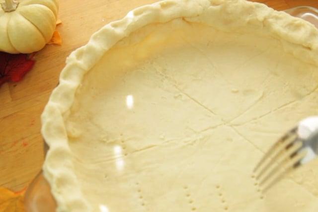 poking vegan pumpkin pie crust using a fork