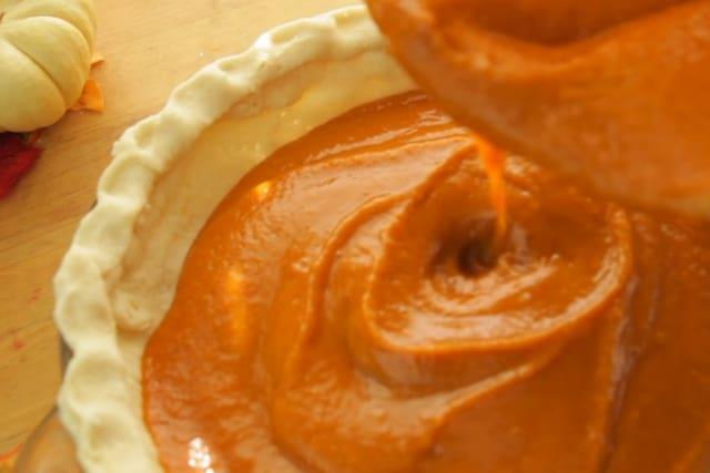 pouring vegan pumpkin pie batter to crust