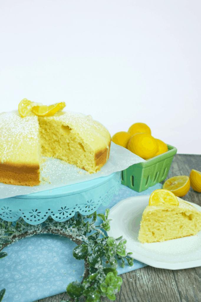 lemon cake on a cake stand with lemons and a sliced lemon cake