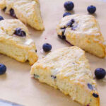Blueberry Scones on parchment paper with fresh blueberries