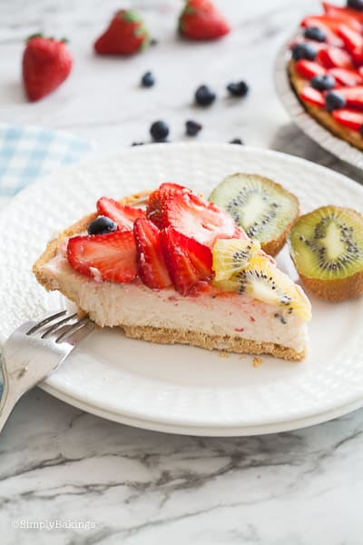 a slice of vegan fruit cheesecake on a white plate with two slices of kiwi