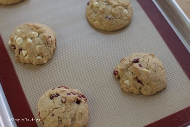 freshly baked cranberry chip cookies on a baking mat