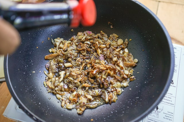 adding soy sauce to the spices and mushroom